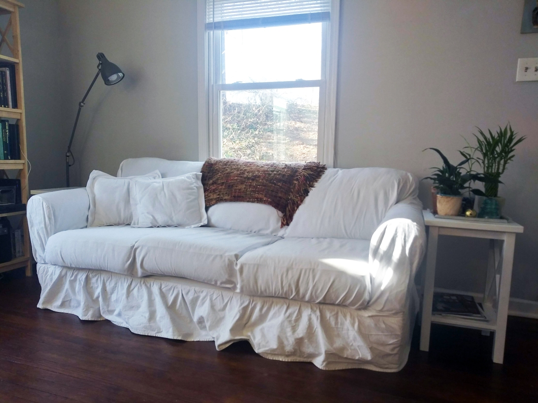 White couch with white end tables and grey accents